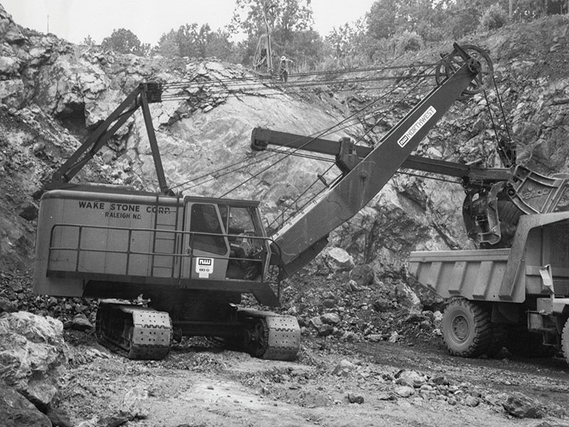 NW Shovel Loading Truck With Driller In Background